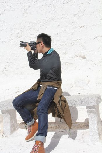 Full Length Of Man Photographing Through Camera While Sitting On Bench By Wall