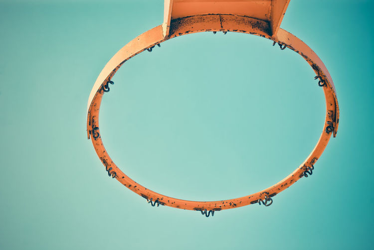 Directly Below Shot Of Old Basket Ball Hoop Against Blue Sky