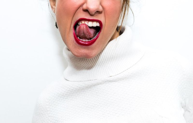 Cropped image of woman sticking out tongue against white background