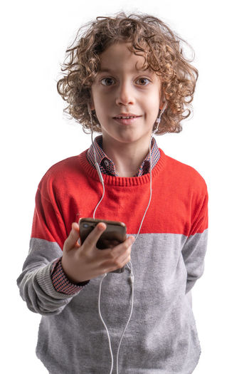 Cute kid using smartphone and wearing an in ear headphone set. Studio shot on a white background Kid Red Backgrounds Childhood Studio Shot Child One Person Portrait Casual Clothing Hairstyle Innocence Looking At Camera Waist Up Holding Indoors  Front View Curly Hair 6 Years Old 7 Years Old White Background Technology Communication Wireless Technology Mobile Phone Connection Hair Listening Listening To Music Hanging Out Holding Smartphone In Ear In Ear Headphones Headphones Headphones On  Smiling New Technologies Concept