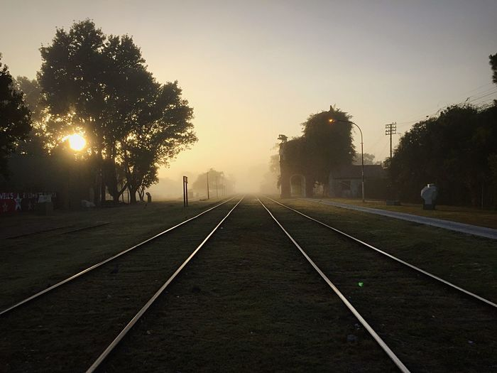 Way Train Rails Plant Tree Sunset Sky Nature The Way Forward Direction Sun No People Diminishing Perspective Tranquility Road Street Beauty In Nature Fog Outdoors Transportation City vanishing point Sunlight