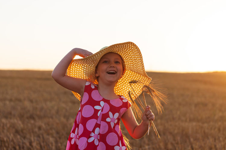 Adorable little girl in a straw hat pink summer dress in wheat field. child with long hair on sunset