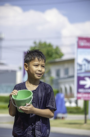 Wet boy holding bucket while standing on road
