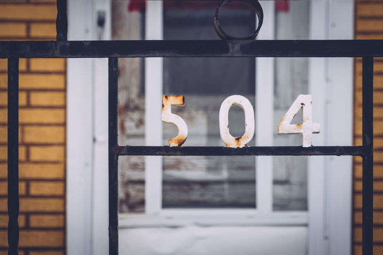 Close-up of numbers on metal against house