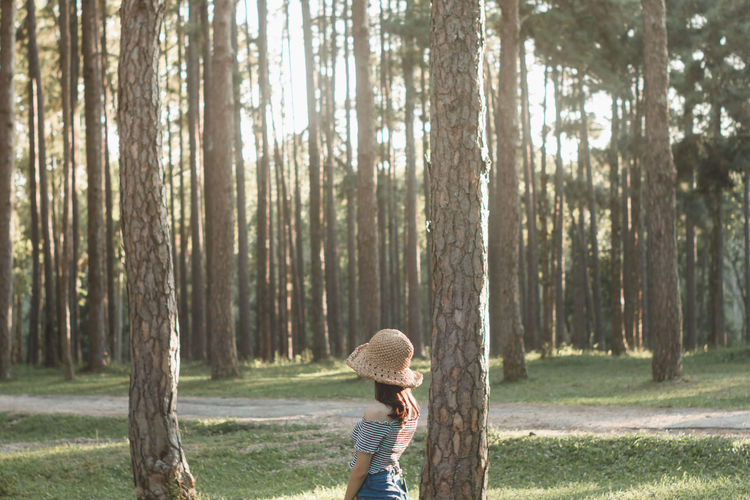 Side View Of Woman Standing By Trees In Forest