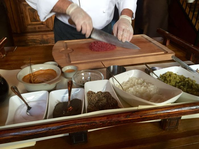 Midsection of male chef chopping beef on table at restaurant