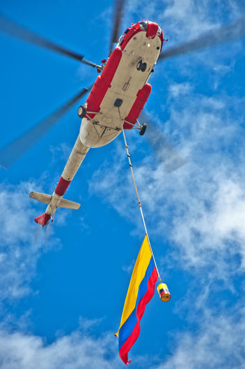 Looking up at a helicopter that is carrying the Colombian flag below it. Aerial Aviation Blue Bogotá Chopper City Colombia Colorful Flag Flight Fly Flying Heli Helicopter Machine Multi Colored Outdoors Power Red Rotor Sky Urban View White Yellow