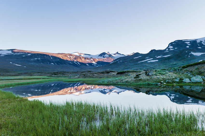 Sunset seen from a valley in Jotunheimen, Norway. Scenics - Nature Water Tranquil Scene Beauty In Nature Tranquility Mountain Landscape Grass Nature Lake Environment Day No People Non-urban Scene Outdoors Jotunheimen Norway Pristine Mountains Valley Hiking Blue Sky EyeEmNewHere