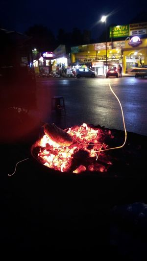 Illuminated fire on street by buildings at night