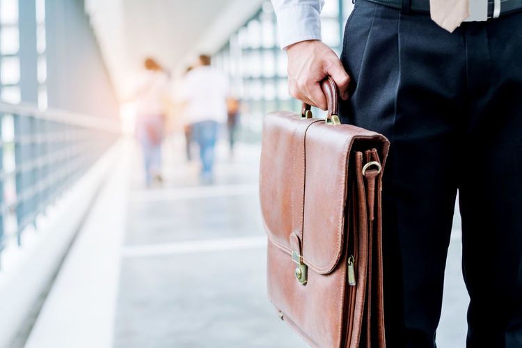 Midsection of businessman holding bag while standing on covered bridge