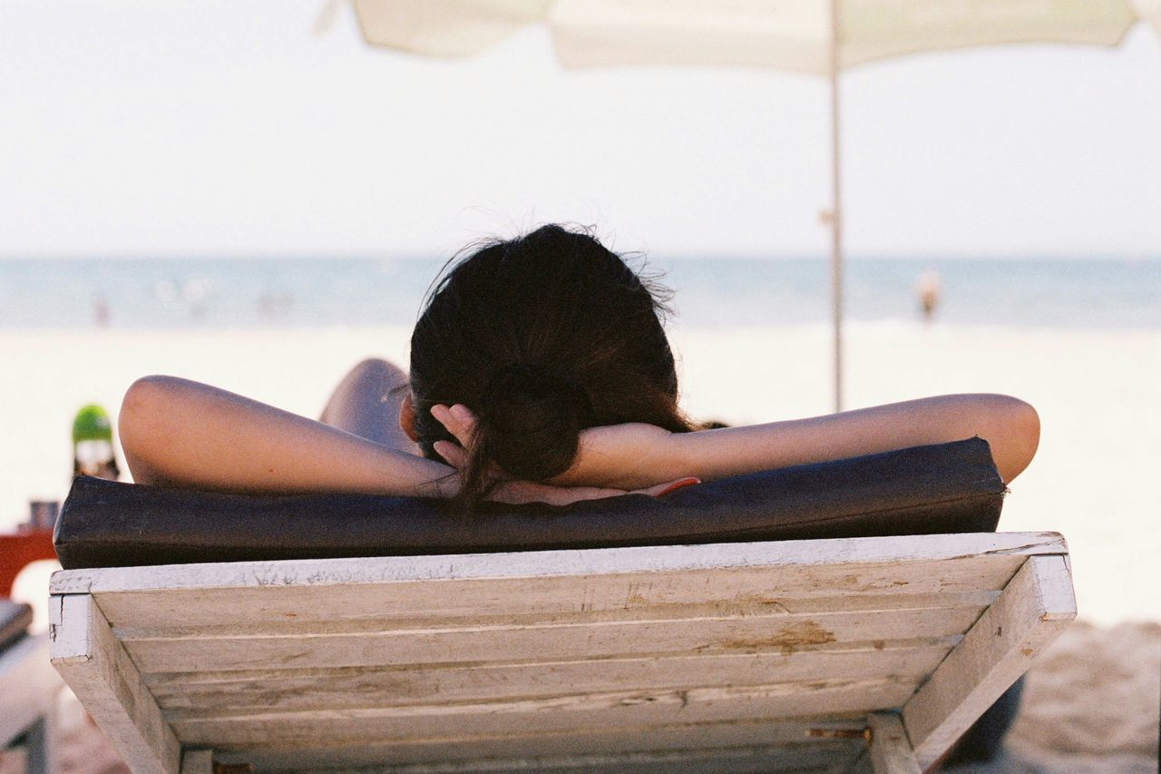 Rear view of woman resting on lounge chair at beach
