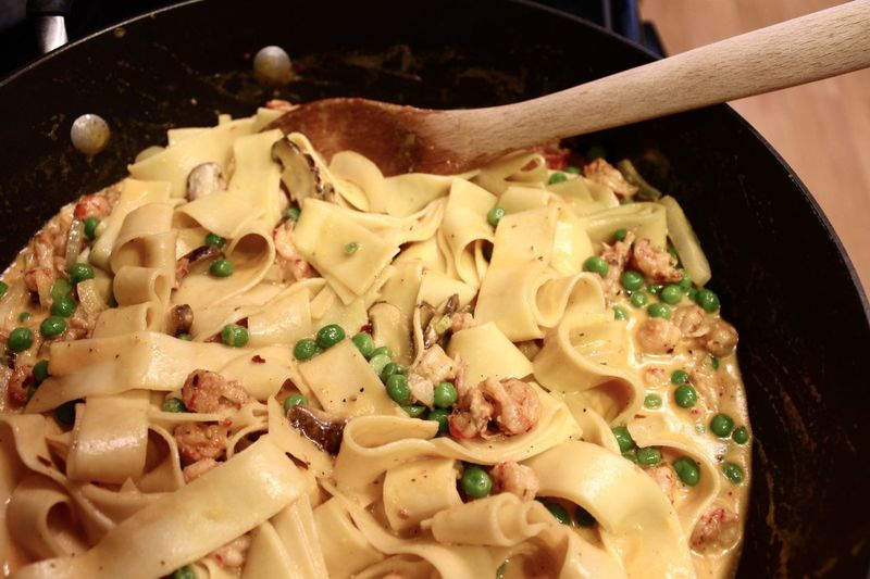 Close-up of pasta with wooden spoon in cooking pan