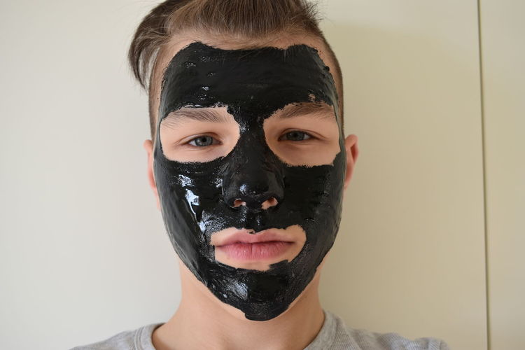 Close-up portrait of teenage boy with black facial mask against wall
