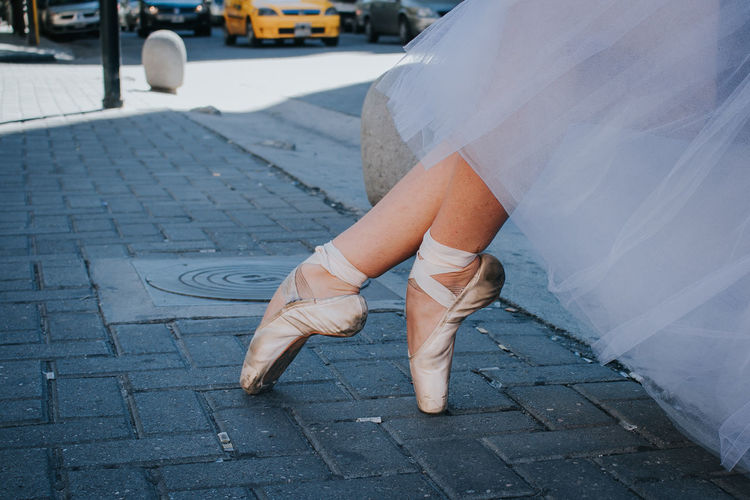 Low section of ballet dancer sitting on street