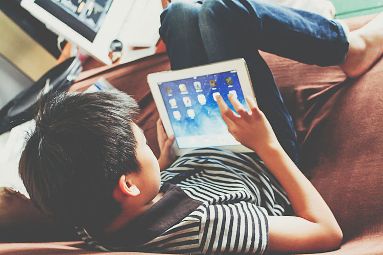iPad Information Device Boy Cyber Child Childhood Communication Connection Digital Tablet Furniture High Angle View Indoors  Innocence Leisure Activity Lifestyles Lying Down Males  One Person Real People Relaxation Screen Technology Wireless Technology Kid Children E-reader Slide - Play Equipment One Baby Boy Only