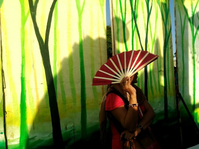 Woman Holding Folding Fan Against Textile
