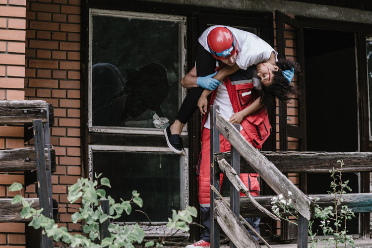 Rescue worker carrying disaster victim out of damaged house
