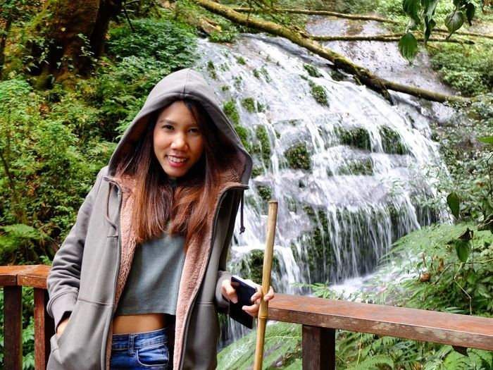 With nature happiness Looking At CameraUniqueness Portrait One Person Lifestyles Real People Leisure Activity Outdoors Warm Clothing Day Front View Green Color Nature Beauty Happiness Water Scarf Smiling Young Women One Woman Only Beautiful Woman Tree Forest Waterfall