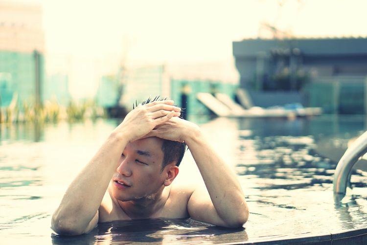Shirtless man adjusting hair in swimming pool