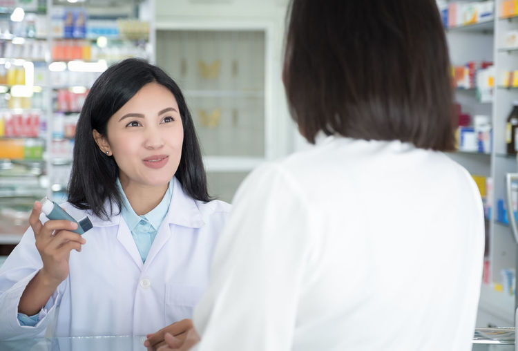Doctor test and teach spray and checking for a patient's mouth Healthcare And Medicine Occupation Two People Women Lab Coat Adult Indoors  Clothing Portrait Females Young Adult Real People Expertise People Young Women Beauty Holding Doctor  Smiling Pharmacy Beautiful Woman
