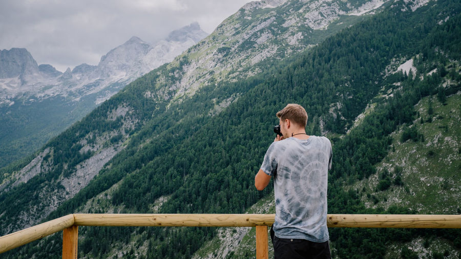 Rear view of man photographing mountains