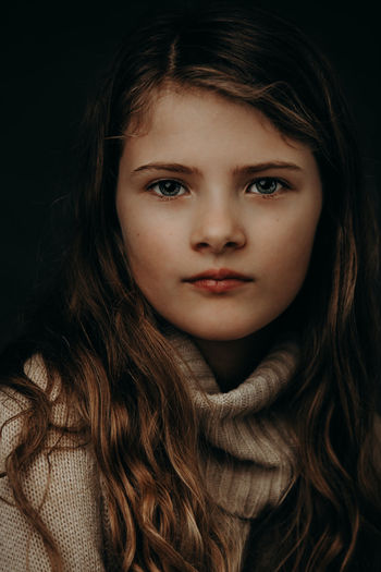 Close-up portrait of cute girl against black background