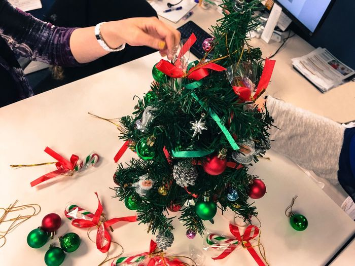 Cropped hands of business people decorating christmas tree at table in office