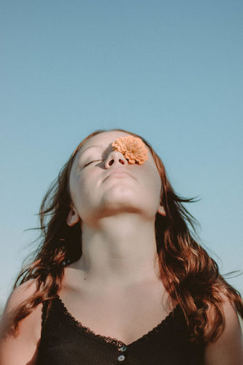 Low angle view of woman with flower on one eye against clear sky