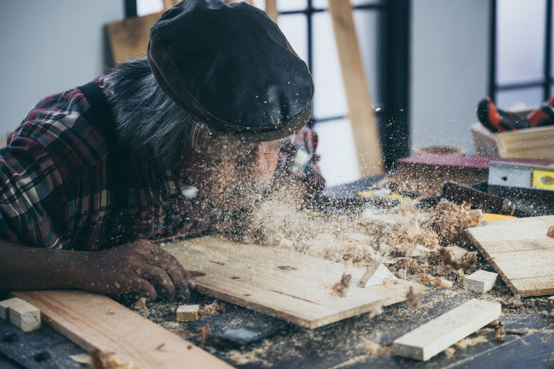 Carpenter with planks on table in workshop
