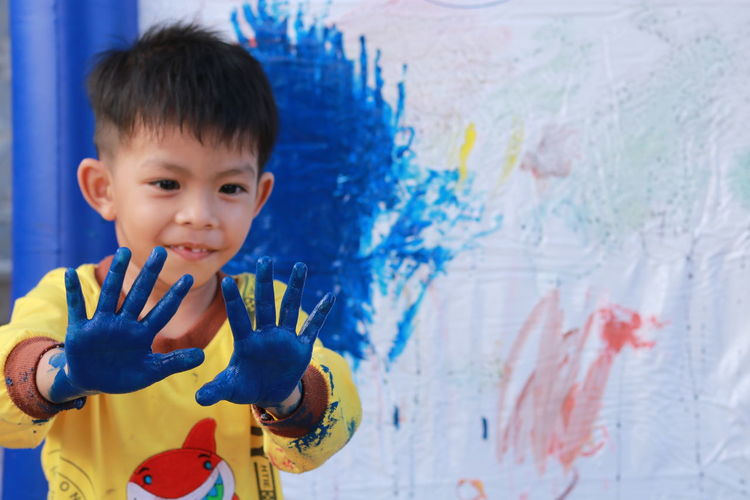 Close-up of cute boy with blue hands against wall