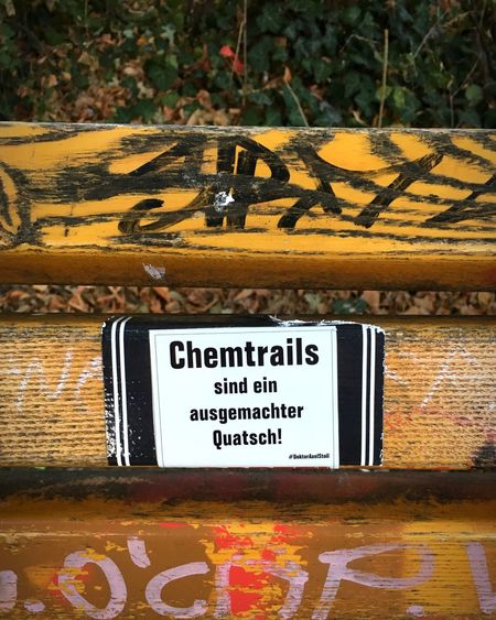 Chemtrails Zentralperspektive Verschwörungstheorie Chemtrails Aufkleber Sticker Bench Text Western Script Communication Day Script Non-western Script No People Sign Wood - Material Information Outdoors Message
