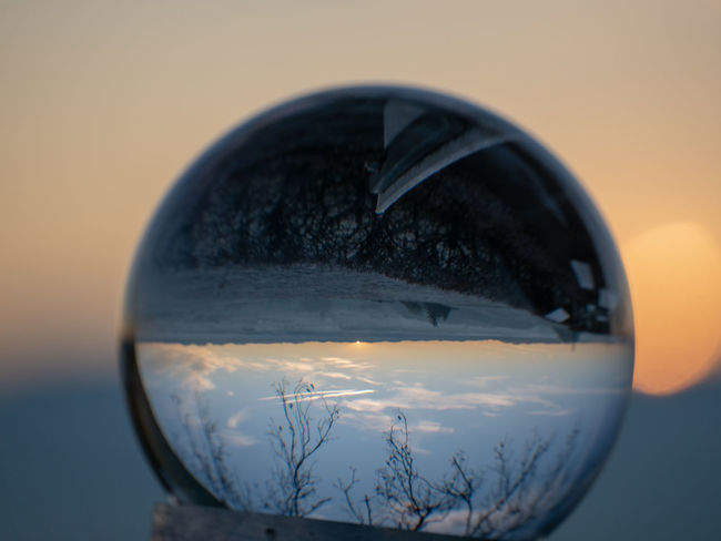 Glass - Material Close-up Sunset Nature No People Reflection Transparent Sky Sphere Tree Focus On Foreground Orange Color Outdoors Still Life Scenics - Nature Geometric Shape Beauty In Nature Winter Shape Circle