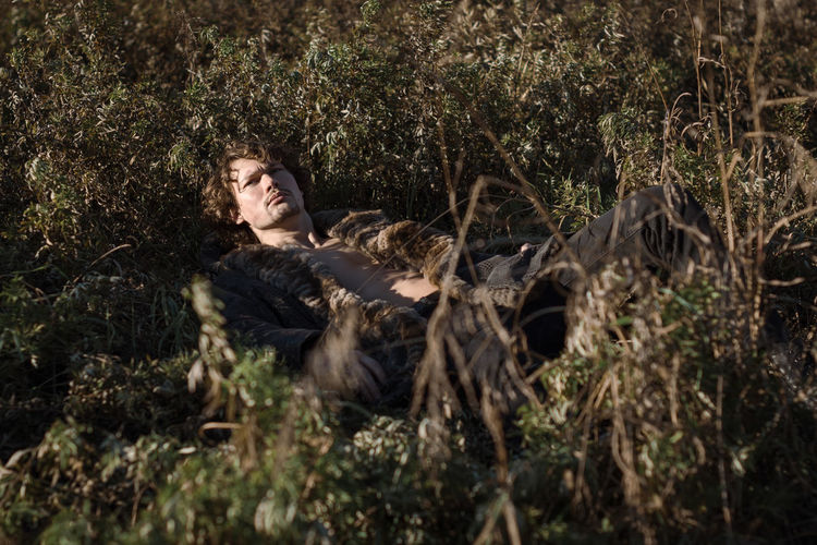 Portrait of man lying down on plants