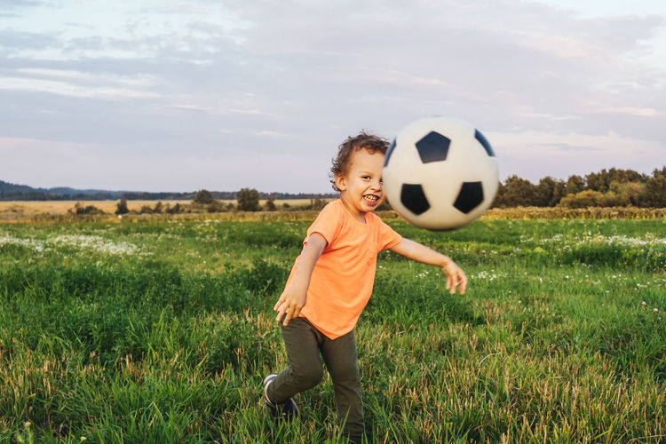 Smiling boy playing with soccer ball on grassy land against sky