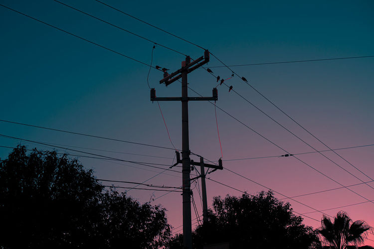 Low angle view of silhouette electricity pylon against sky at sunset