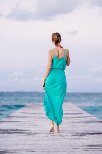 Walking away Lifestyle Beach Beauty In Nature Dock Dress Full Length Horizon Over Water Leisure Activity Lifestyles One Person Outdoors People Real People Rear View Sea Sky Standing Walking Water Young Adult Young Women