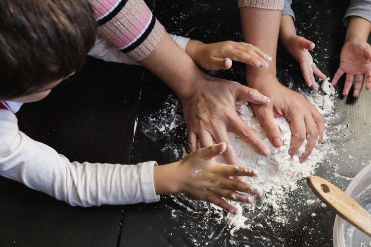 High angle view of people hands in water