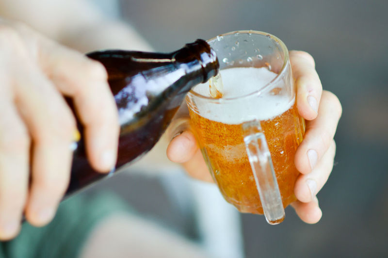 Cropped Hand Of Man Pouring Beer In Glass From Bottle