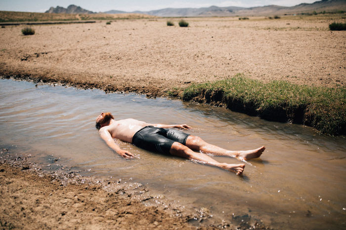 SIDE VIEW OF SHIRTLESS MAN LYING IN WATER AT SHORE