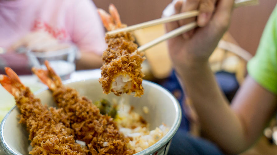 Cropped Hand Of Person Holding Katsu With Chopsticks Over Bowl