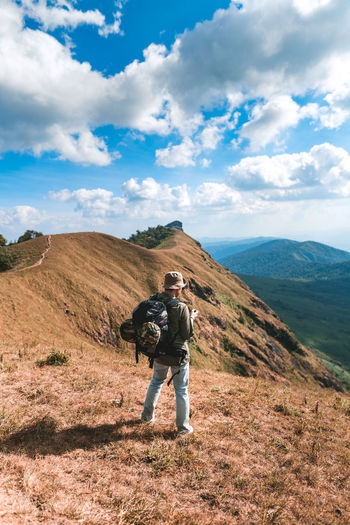 Full length of man with umbrella on mountain against sky