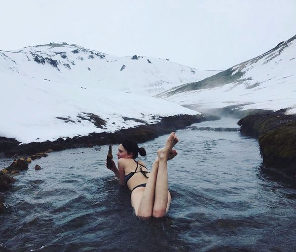 Young woman holding beer bottle while lying in stream amidst snowcapped mountain