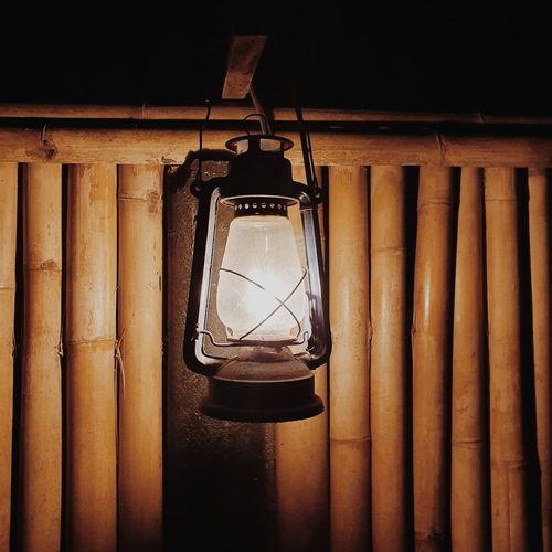 Close-up of illuminated lamp hanging on wall