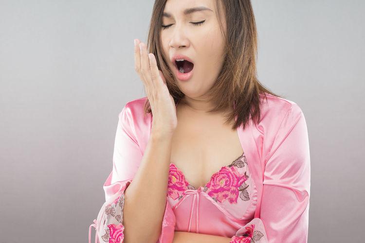 Woman in nightwear yawning against wall