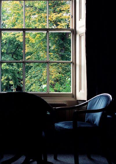 Empty chair seen through glass window