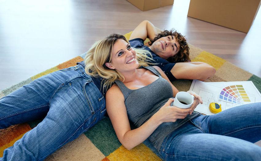 High angle view of couple lying on rug at home
