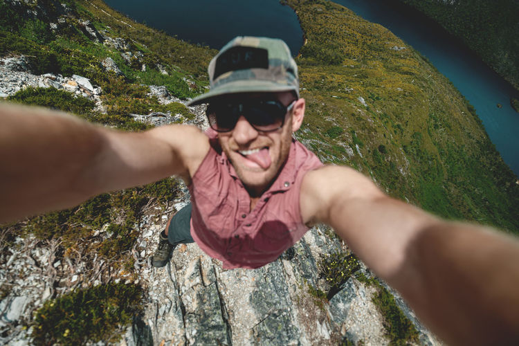 High angle portrait of man wearing sunglasses while standing on mountain