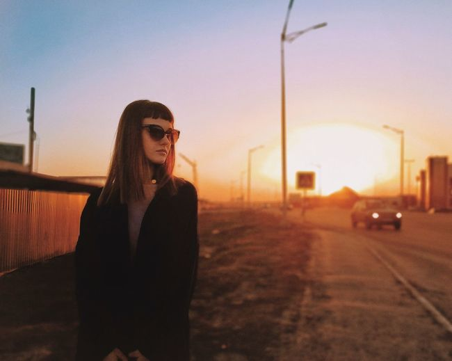Young woman wearing sunglasses standing by road against sky during sunset