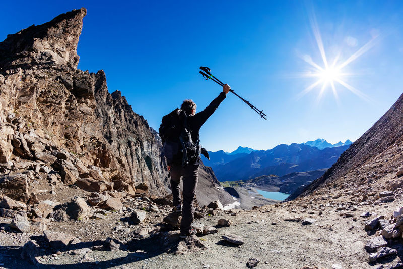 Full length rear view of mature man holding hiking poles standing at mountain