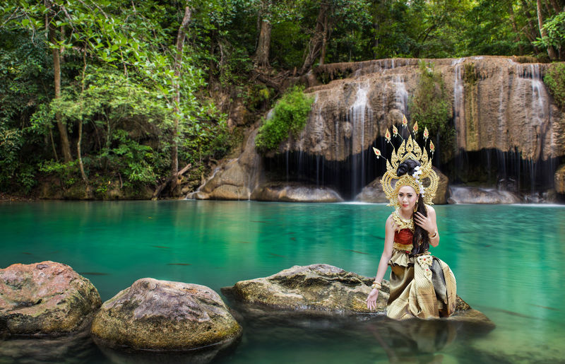 Portrait of beautiful young woman wearing crown and traditional clothing while sitting on rock against lake at forest